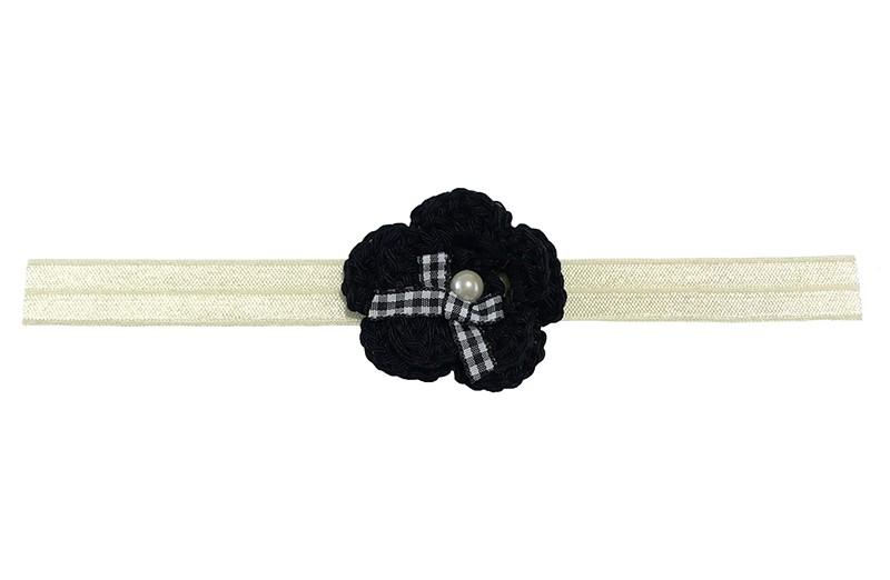 Lief creme baby haarbandje. Met een zwart gehaakt bloemetje.  Afgewerkt met een zwart wit geruit strikje en een pareltje.  Het haarbandje is van rekbaar elastiek. Niet uitgerekt is het haarbandje ongeveer 18.5 centimeter.