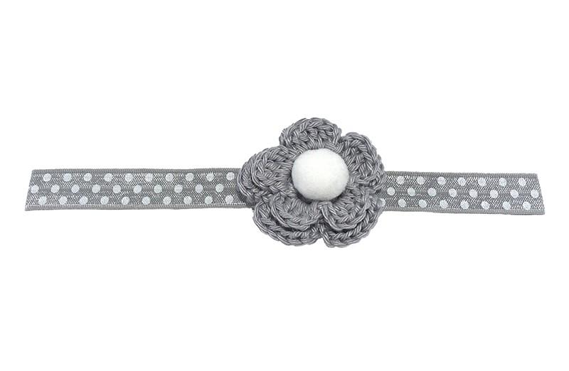 Lief glanzend grijs baby haarbandje met witte stippeltjes. Met daarop een gehaakte grijze bloem.  Afgewerkt met een zachte witte pompom.  Het bandje is niet uitgerekt ongeveer 18 centimeter.  Het gehaakte bloemetje is ongeveer 5 centimeter.