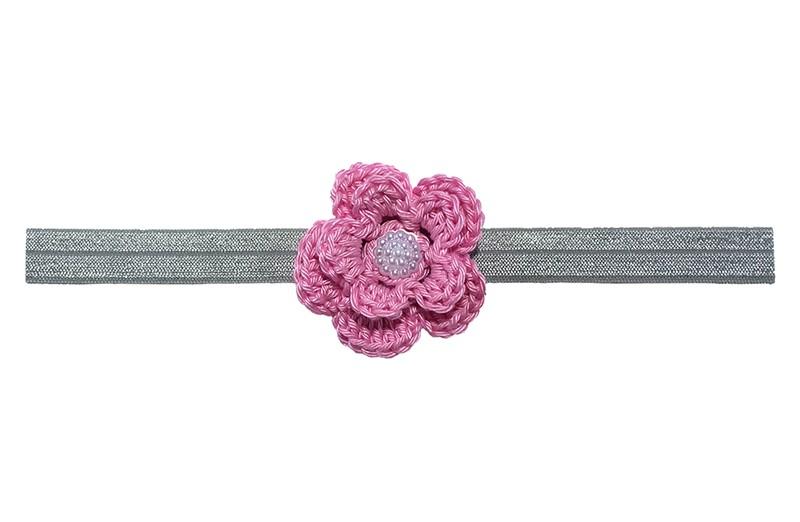Schattig grijs glanzend baby haarbandje van rekbaar elastiek.  Met een roze gehaakt bloemetje van ongeveer 5 centimeter. Afgewerkt met een wit pareltje.  Niet uitgerekt is de omtrek van het haarbandje ongeveer 38 centimeter. Het haarbandje is ongeveer 1.5 centimeter breed.