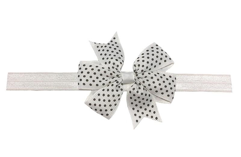 Vrolijk wit baby haarbandje. Met een witte strik met zwarte stippeltjes. De strik is ongeveer 8 centimeter.  Het haarbandje is van rekbaar elastiek. Niet uitgerekt is het haarbandje ongeveer 17 centimeter.