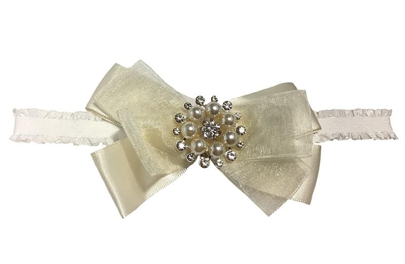 Schattig wit baby haarbandje met een grote ivoorkleurige strik van 2 soorten lint. Afgemaakt met mooie parels.  Niet uitgerekt is het haarbandje ongeveer 16,5 centimeter.  De strik is ongeveer 7 centimeter.