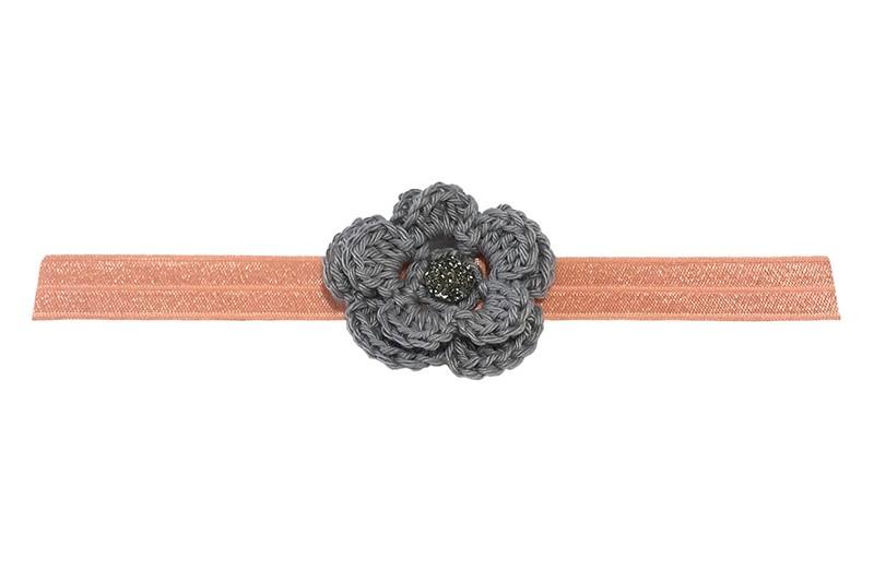 Leuk glanzend zalm roze / licht oranje baby haarbandje met een grijs gehaakt bloemetje.  Afgewerkt met een grijs glinstersteentje.  Niet uitgerekt is het haarbandje ongeveer 18.5 centimeter.  Het gehaakte bloemetje is ongeveer 5 centimeter.