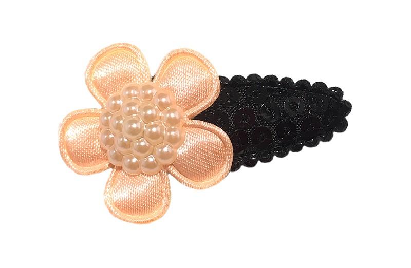 Leuk zwart baby haarspeldje met kleine zwarte pailletjes. Met een effen licht oranje bloemetje. Afgewerkt met een mooie parel.