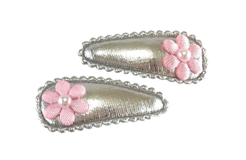 Vrolijk setje van 2 zilver glanzende baby peuter haarspeldjes met op elk een klein licht roze bloemetje en een klein wit pareltje.