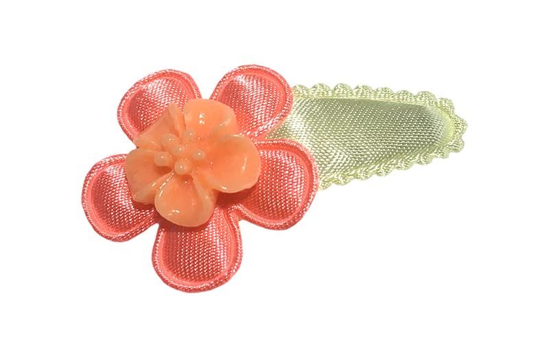 Vrolijk zacht geel baby peuter haarspeldje.  Met een effen koraalroze bloemetje en een oranje steentje in de vorm van een bloemetje.