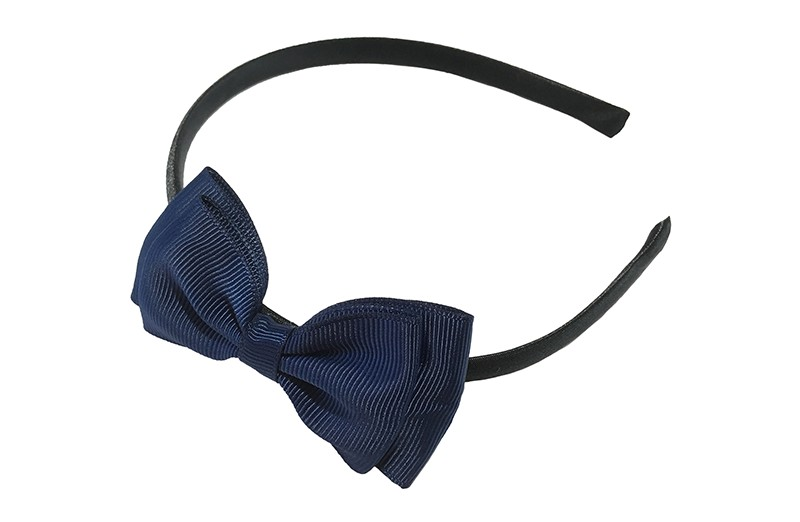 Vrolijke donkerblauwe meisjes diadeem. Bekleed met glanzend donkerblauw lint. Met daarop een dubbellaagse strik van heel donker blauw lint.  Deze diadeem is zonder tandjes. Het strikje is ongeveer 8 centimeter breed. Geschikt voor ongeveer 2 - 6jaar.