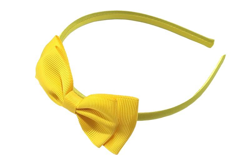 Vrolijke gele meisjes diadeem. Bekleed met glanzend licht geel lint. Met daarop een dubbellaagse strik van geel lint.  Deze diadeem is zonder tandjes. Het strikje is ongeveer 8 centimeter breed. Geschikt voor ongeveer 2 - 6jaar.