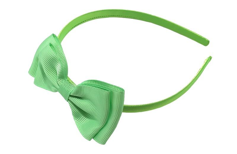 Vrolijke groene meisjes diadeem. Bekleed met glanzend fel groen lint. Met daarop een dubbellaagse strik van licht groen lint.  Deze diadeem is zonder tandjes. Het strikje is ongeveer 8 centimeter breed. Geschikt voor ongeveer 2 - 6jaar.