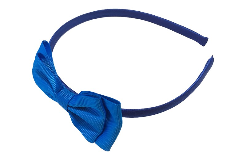 Vrolijke kobalt blauwe meisjes diadeem. Bekleed met glanzend donkerblauw blauw lint. Met daarop een dubbellaagse strik van kobalt blauw lint.  Deze diadeem is zonder tandjes. Het strikje is ongeveer 8 centimeter breed. Geschikt voor ongeveer 2 - 6jaar.