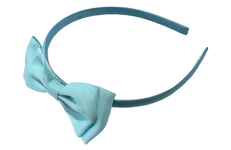 Vrolijke licht blauwe meisjes diadeem. Bekleed met glanzend licht blauw lint. Met daarop een dubbellaagse strik van licht blauw lint.  Deze diadeem is zonder tandjes. Het strikje is ongeveer 8 centimeter breed. Geschikt voor ongeveer 2 - 6jaar.