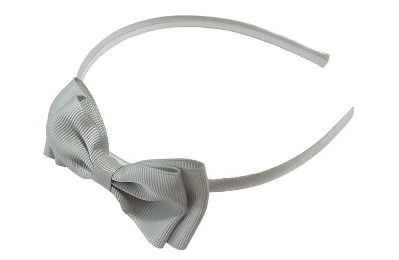 Vrolijke grijze meisjes diadeem. Bekleed met glanzend zilvergrijs lint. Met daarop een dubbellaagse strik van grijs lint.  Deze diadeem is zonder tandjes. Het strikje is ongeveer 8 centimeter breed. Geschikt voor ongeveer 2 - 6jaar.