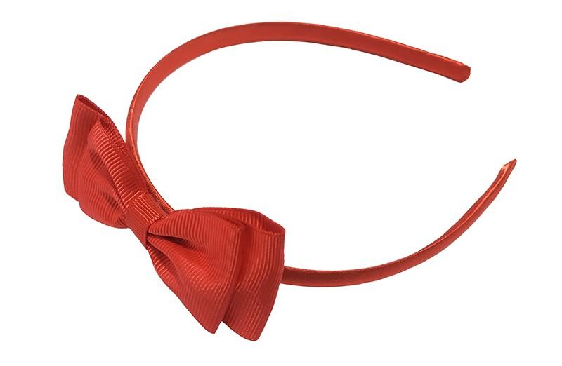 Vrolijke rode meisjes diadeem. Bekleed met glanzend rood lint. Met daarop een dubbellaagse strik van rood lint.  Deze diadeem is zonder tandjes. Het strikje is ongeveer 8 centimeter breed. Geschikt voor ongeveer 2 - 6jaar.