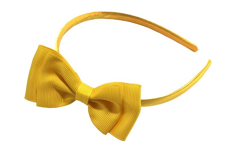Vrolijke gele meisjes diadeem. Bekleed met glanzend geel lint. Met daarop een dubbellaagse strik van geel lint.  Deze diadeem is zonder tandjes. Het strikje is ongeveer 8 centimeter breed. Geschikt voor ongeveer 2 - 6jaar.