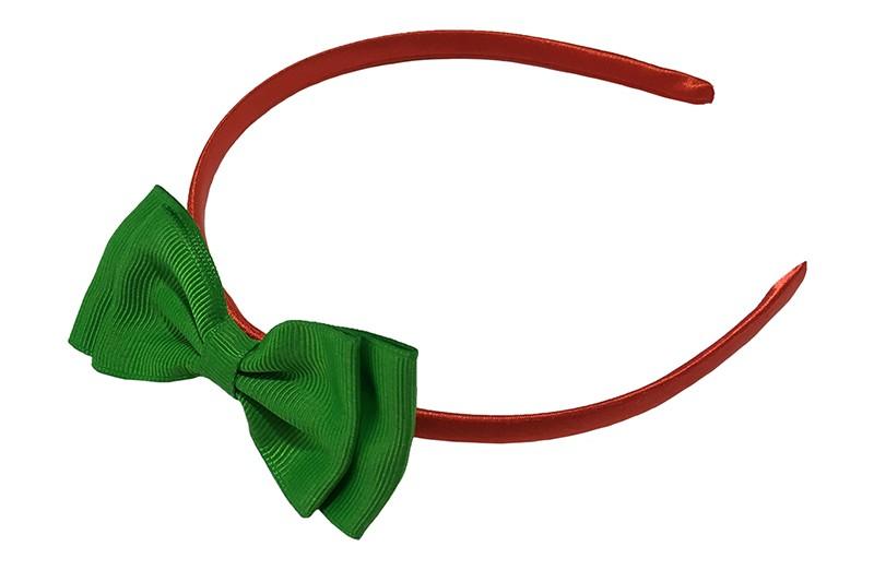 Vrolijke rood groene meisjes diadeem. Bekleed met glanzend rood  lint. Met daarop een dubbellaagse strik van groen lint.  De diadeem is zonder tandjes. Het strikje is ongeveer 8 centimeter breed. Geschikt voor ongeveer 2 - 6jaar.