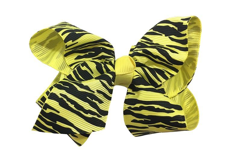 Leuke grote gele meisjes haarstrik van lint met zebra printje. Op een platte haarknip van 4.5 centimeter bekleed met geel  lint. De strik heeft een afmeting van ongeveer 10 centimeter.