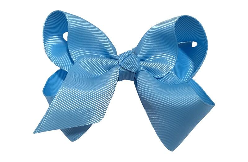 Leuke grote effen licht blauwe meisjes haarstrik van lint. Op een platte haarknip van 4.5 centimeter bekleed met lichtblauw lint. De strik heeft een afmeting van ongeveer 10 centimeter.