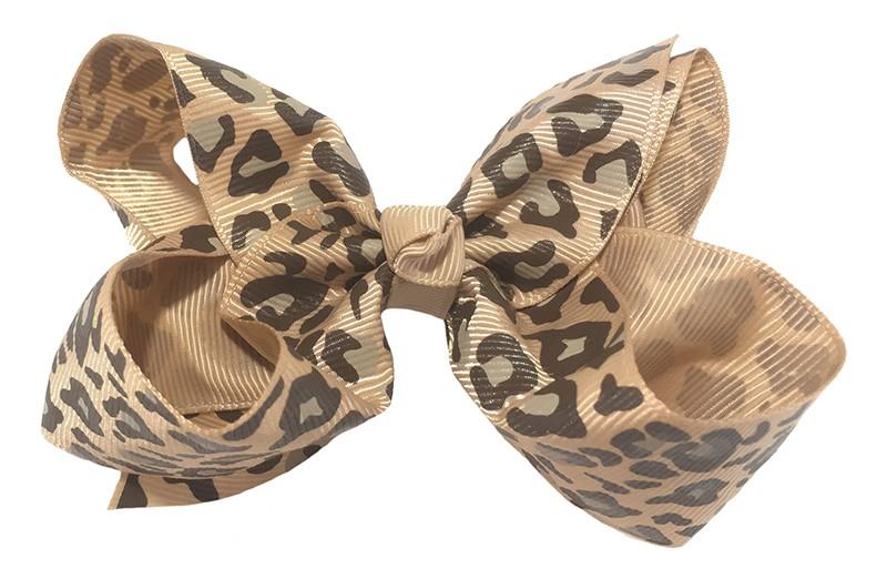 Leuke grote licht bruine meisjes haarstrik van lint met luipaard printje. Op een platte haarknip van 4.5 centimeter bekleed met licht bruin lint. De strik heeft een afmeting van ongeveer 10 centimeter.