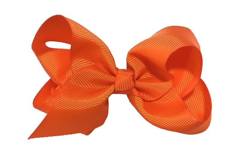 Leuke grote effen oranje meisjes haarstrik van lint. Op een platte haarknip van 4.5 centimeter bekleed met oranje lint. De strik heeft een afmeting van ongeveer 10 centimeter.