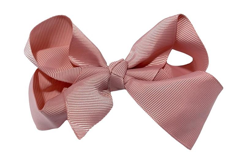 Leuke grote effen oud roze meisjes haarstrik van lint. Op een handige haarknip van ongeveer 5.5 centimeter met kleine tandjes. De strik heeft een afmeting van ongeveer 10 centimeter.
