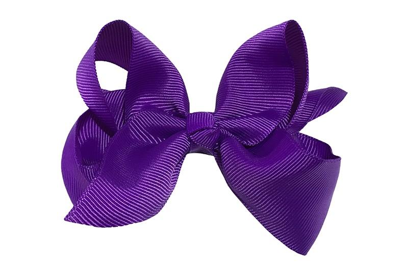 Leuke grote effen paarse meisjes haarstrik van lint. Op een platte haarknip van 4.5 centimeter bekleed met paars lint. De strik heeft een afmeting van ongeveer 10 centimeter.
