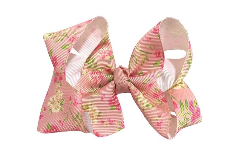 Leuke grote roze haarstrik van lint met een vrolijk bloemetjes dessin.  In een leuk dubbelgeknoopt model.  Op een handige haarknip met tandjes van ongeveer 5.5 centimeter.
