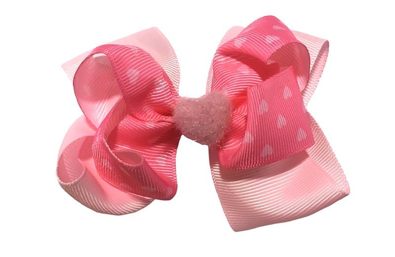 Lief roze dubbellaags meisjes haarstrikje. Het haarstrikje is van effen lichtroze lint en fel roze lint met licht roze hartjes. Afgewerkt met een licht roze fluffie hartje.  Het strikje is makkelijk in het haar te zetten met een alligator haarknipje van ongeveer 5.5 centimeter.