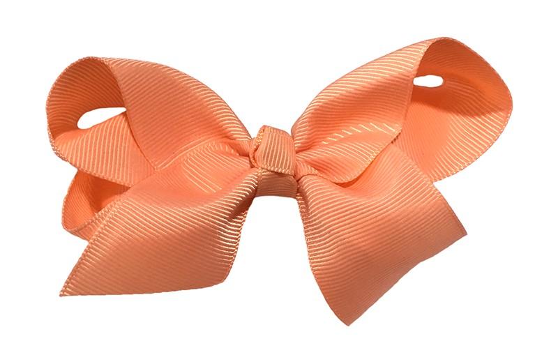 Leuke grote effen zalmroze meisjes haarstrik van lint. Op een platte haarknip van 4.5 centimeter bekleed met zalm roze lint. De strik heeft een afmeting van ongeveer 10 centimeter.