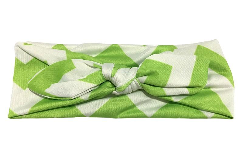 Vrolijk groen wit baby peuter haarbandje van gladde rekbare stof met zigzag strepen. Geknoopt in leuk 'konijnenoortjes model'. De hoogte van het haarbandje is ongeveer 6 centimeter.