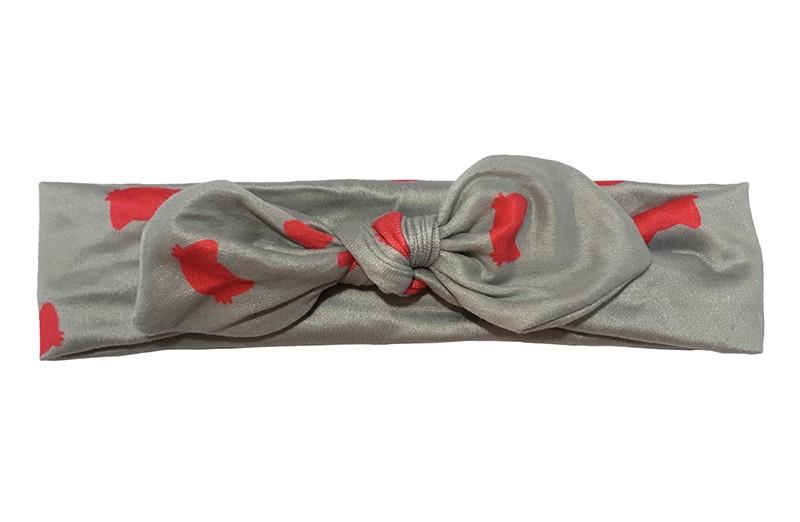 Leuk grijs stoffen peuter meisjes haarbandje.  Met een vrolijke rode figuurtjes.  Het haarbandje is van gladde rekbare stof.  Geknoopt in een leuk modelletje.  Het haarbandje is geschikt tot en met ongeveer 5 jaar.