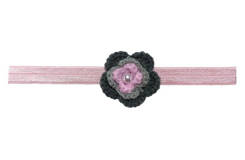 Schattig licht roze, glanzend, baby haarbandje van rekbaar elastiek.  Met een grijs/roze gehaakt bloemetje van ongeveer 4 centimeter. Afgewerkt met een wit pareltje.  Niet uitgerekt is de omtrek van het haarbandje ongeveer 38 centimeter. Het haarbandje is ongeveer 1.5 centimeter breed.