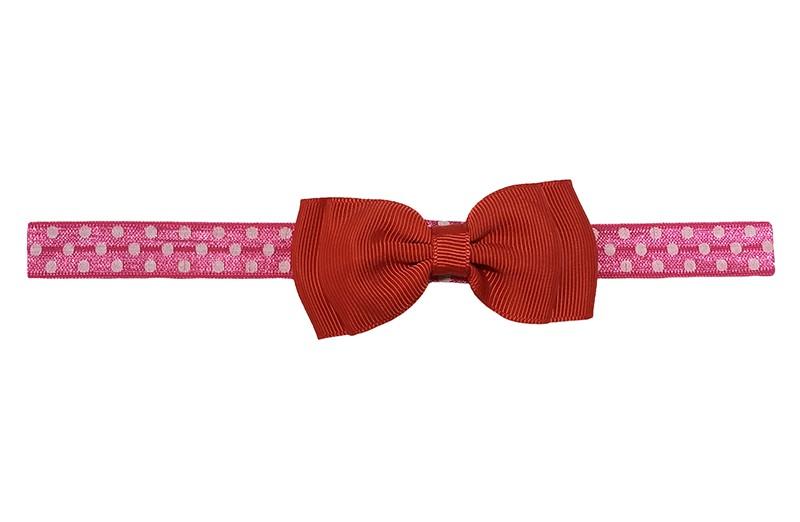 Vrolijk fel roze peuter kleuter meisjes haarbandje met witte stippeltjes.  Met een rood dubbellaags strikje van lint.  Het haarbandje is van rekbaar elastiek, geschikt tot en met ongeveer 5 jaar.