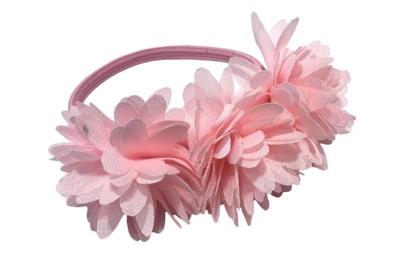Schattige licht roze haarelastiek/knotbandje met 3 licht roze chiffon bloemen. Leuk in de haartjes van de meiden bij een leuk vrolijk knotje bijvoorbeeld.  Het licht roze elastiekje heeft een doorsnee van ongeveer 5.5 centimeter.