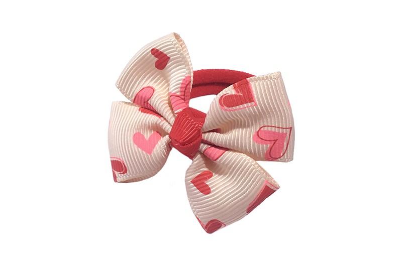 Vrolijk rood haarelastiekje. Met een cremekleurig strikje met roodroze hartjes printje.  Het strikje is ongeveer 5 centimeter.
