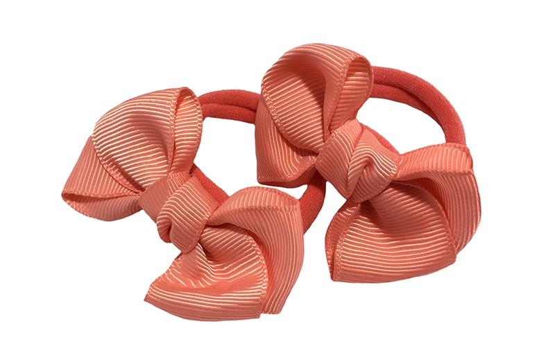Vrolijk setje van 2 oranje zachte haarelastiekjes met op elk een leuk koraalroze / zalmroze strikje van lint.