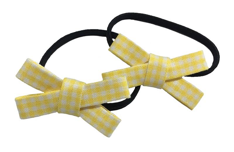 Lief setje van 2 smalle zwarte haarelastiekjes. Met op elk een geel geruit stoffen strikje. De strikjes zijn ongeveer 3.5 centimeter breed.