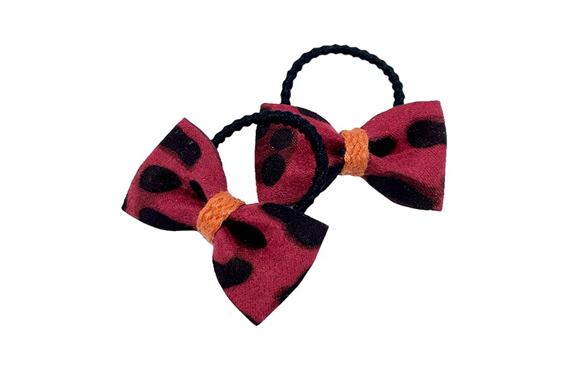 Schattig setje van 2 kleine zwarte haarleastiekjes.  Met op elk een rood zacht stoffen strikje met bruin zwart dierendessin.