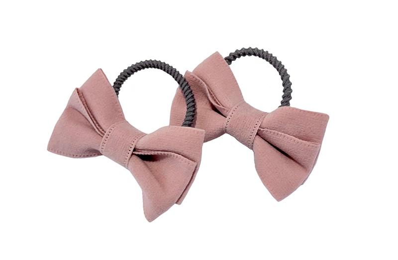 Schattig setje van 2 smalle taupe grijze haarelastiekjes.  Met op elk een roze vilten strikje in een mooie dubbelgestrikte look.  De elastiekjes hebben kleine ribbeltjes waardoor ze beter blijven zitten in de haartjes.  De strikjes zijn ongeveer 5 centimeter breed.