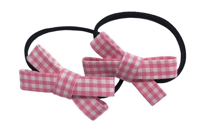 Lief setje van 2 smalle zwarte haarelastiekjes. Met op elk een licht roze geruit stoffen strikje. De strikjes zijn ongeveer 3.5 centimeter breed.