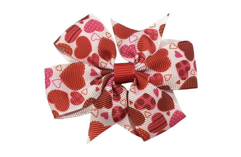 Leuke witte haarstrik van lint. Met een vrolijk dessin van rode en roze hartjes.  Op een platte haarknip bekleed met rood lint.