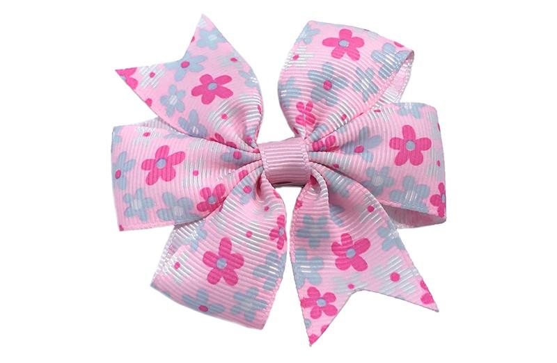 Vrolijke licht roze haarstrik met kleine roze en blauwe bloemetjes erop. Op een alligator knipje.