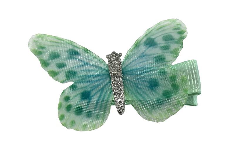 Vrolijk licht groen peuter haarknipje met licht groen en zilver vlindertje. Het knipje is 3.5 centimeter en bekleed met licht blauw lint.