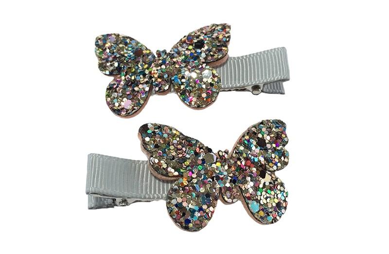 Schattig setje van 2 zilvergrijze haarknipjes. Met op elk een vlindertje in zilver glitterlook.  Het haarknipje is ongeveer 5 centimeter en is bekleed met zilvergrijs lint.