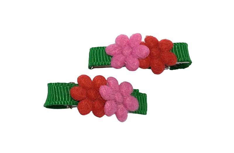 Vrolijk setje van 2 mini haarknipjes met kleine tandjes. Bekleed met groen lint.  Met op elk een klein rood en roze bloemetje.