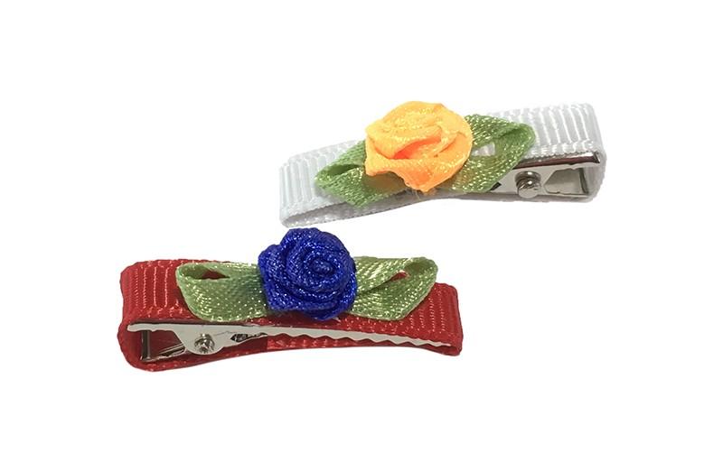 Schattig setje van 2 kleine, smalle haarknipjes. 1 knipje bekleed met rood lint en een blauw roosje. En 1 knipje bekleed met wit lint met een oranje roosje. Met op elk een cremekleurig roosje. Het knipje is een alligator knipje van ongeveer 3 centimeter.