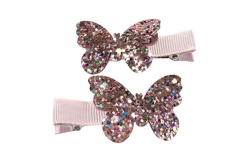 Schattig setje van 2 lichtroze haarknipjes.  Met op elk een vlindertje in glitterlook.  Het haarknipje is ongeveer 5 centimeter en is bekleed met lichtroze lint.