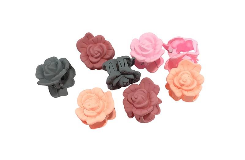 Vrolijk setje van 8 kleine haarknipjes in de vorm van een bloemetje.  In verschillende kleuren roze en grijs.  Handig om bijvoorbeeld haarplukjes in een knotje vast te zetten of een plukje haar even vast te knippen.