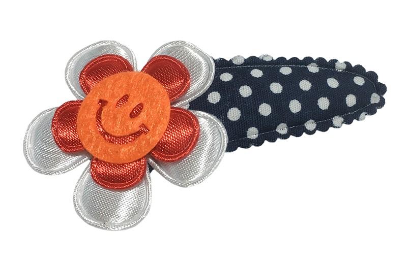 Vrolijk donkerblauw peuter kleuter haarspeldje met witte stippeltjes.  Met daarop een effen wit bloemetje en een effen rood bloemetje. Afgewerkt met een vrolijke oranje smiley.