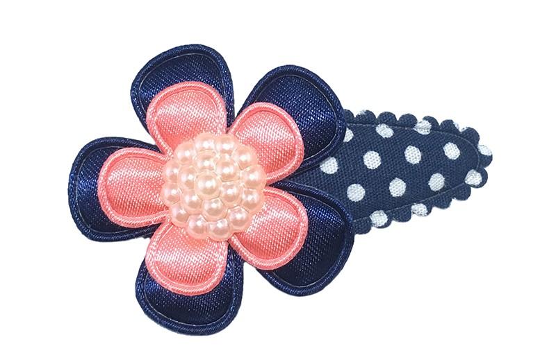 Leuk donkerblauw haarspeldje met witte stippeltjes. Met daarop een effen glanzende donkerblauwe bloem en een klein effen koraalroze bloemetje. Afgewerkt met een mooie creme kleurige parel.