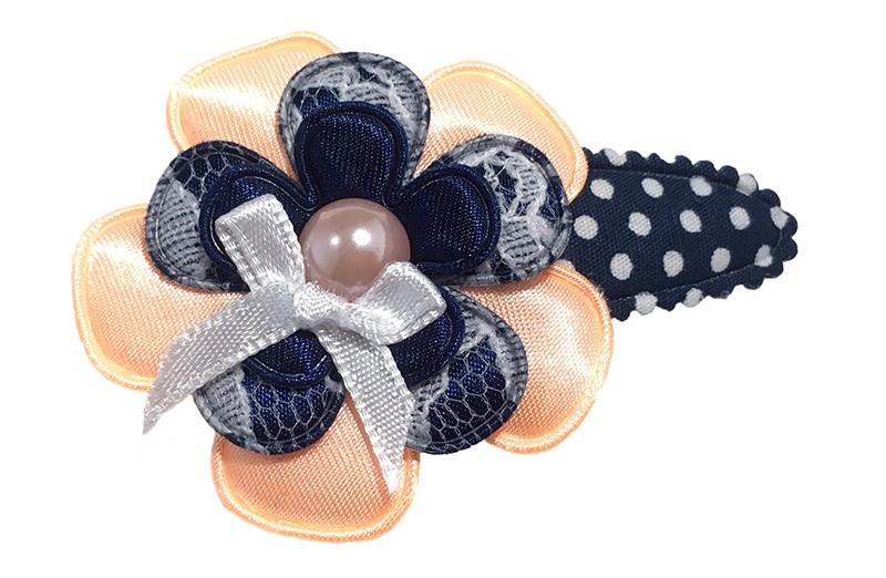 Vrolijk donkerblauw peuter kleuter haarspeldje met witte stippeltjes. Met effen licht oranje glanzend bloemetje, een donkerblauw bloemetje in kantlook en een effen donkerblauw bloemetje.  Afgewerkt met een licht oranje parel en een klein wit strikje.