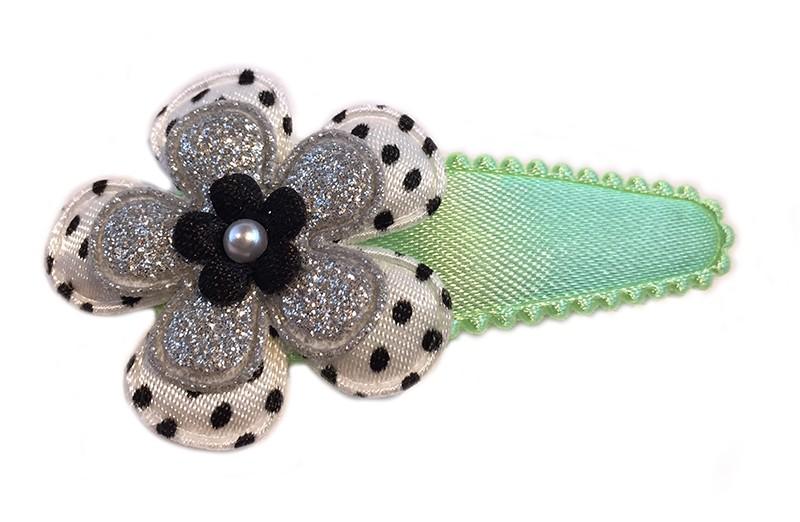Leuk effen mint groen haarspeldje. Met wit bloemetje, zwart gestippeld en een zilver glitter bloemetje. Afgewerkt met een mini zwart bloemetje en een pareltje.